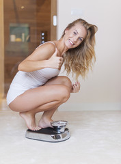 Happy woman on weighing scale showing thumb up
