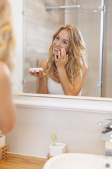 Blonde woman applying moisturizer on face