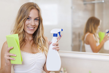 Happy blonde woman is ready to cleaning bathroom