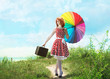 Retro style redheaded girl walking with a colorful umbrella