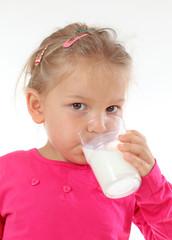 Little girl drinking glass of milk