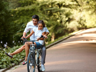 Happy couple cycling in the summer park
