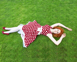 Smiling girl lying on the grass, view from above