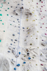 Ropes Footholds and Bells on Rock Climbing Wall