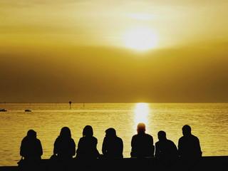 Tourists sitting on the seashore watching sunset