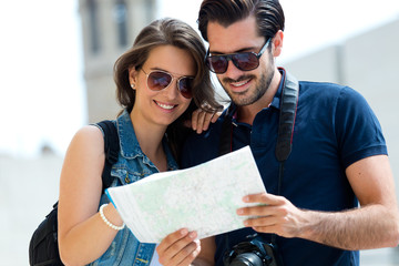 Young tourist couple in town holding a map.