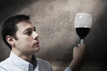 Young man looking at a glass of wine