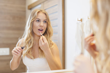 Blonde woman finishing makeup in front of mirror