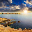 ancient city on a rocky shore near sea at sunset