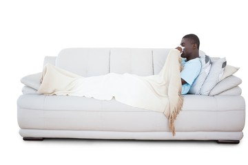 Sick man lying on couch blowing his nose