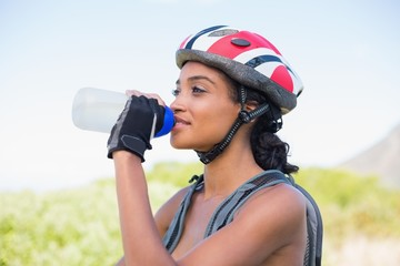 Fit woman going for bike ride drinking water