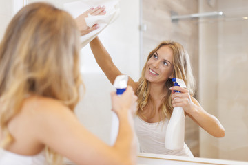 Young blonde woman cleaning mirror in bathroom