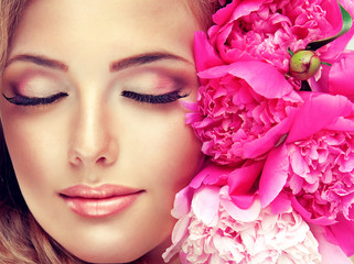 Beautiful face model , with a smile and flowers near the face .