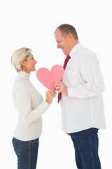 Older affectionate couple holding pink heart shape