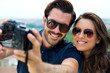 Young tourist couple taking photo of themselves.