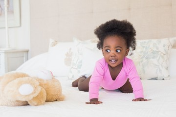 Baby girl in pink babygro crawling on bed