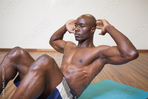 canvas print picture Muscular man doing abdominal crunches in gym