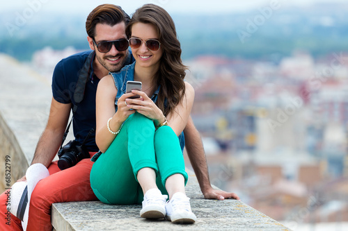 Young couple of tourist in town using mobile phone. - 68522799