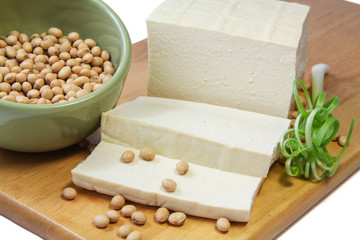 Tofu and Soybean on a chopping block with green onion.