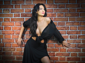 Charming young brunette woman in black near the brick wall