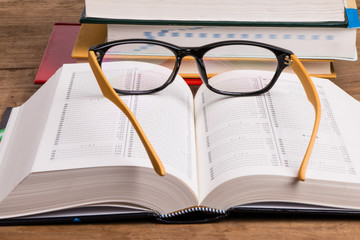 eyeglasses and books on wooden background