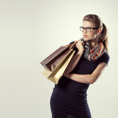Portrait of trendy shopper standing with shopping bags