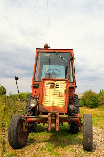 Old Russian tractor in the yard of a farm