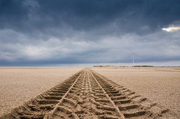 Tyre tracks on the sand of the beach