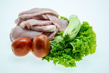 Pieces of raw pork meat and vegetables on white background