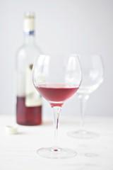 Wein im Glas und Weinflasche im Hintergrund