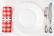 Vintage cutlery set with fork, knife, plate and red napkin.