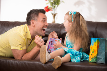 Cute little girl having fun with presents
