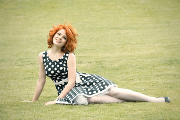 Smiling redheaded girl sitting on the grass and smiling