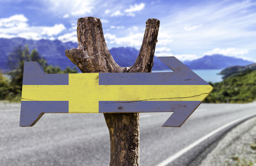 Sweden wooden sign with a landscape on background