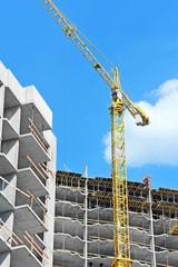 Crane and building construction site against blue sky
