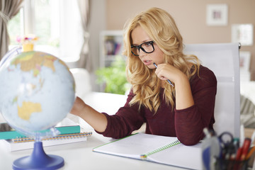 Focus girl studying globe of earth at home