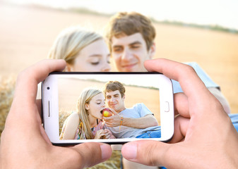 Hands taking photo young couple in love with smartphone