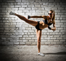 Muscular woman on brick wall (dark version)