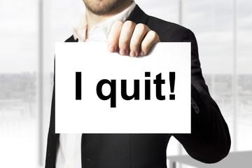 businessman holding sign i quit