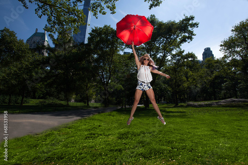 Young Blonde Athletic woman holding a Red Umbrella in Central Pa Poster