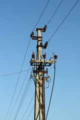 Pole with electrical cables on blue sky background