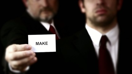 Businessmen showing a card with text