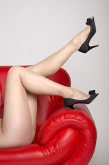 Legs in light coloured tights on a red sofa
