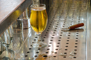 single beer glass and bottle opener behind the bar counter