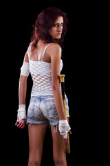 Fearful young street fighter girl on a black background.