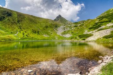 Amazing mountain lake and stony peak