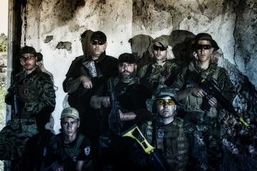 Airsoft group team in daytime action in pose