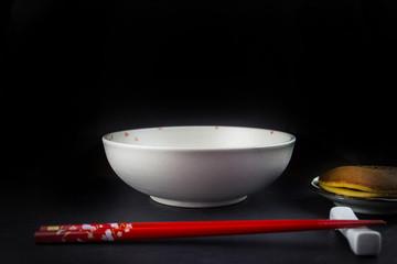 Reisschüssel, Stäbchen und japanische Süßigkeit