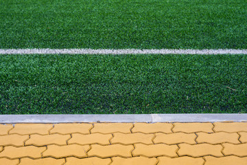 Soccer field grass with orange brick platform