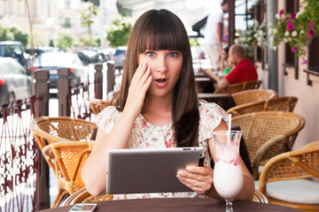 Woman uses the tablet in cafe